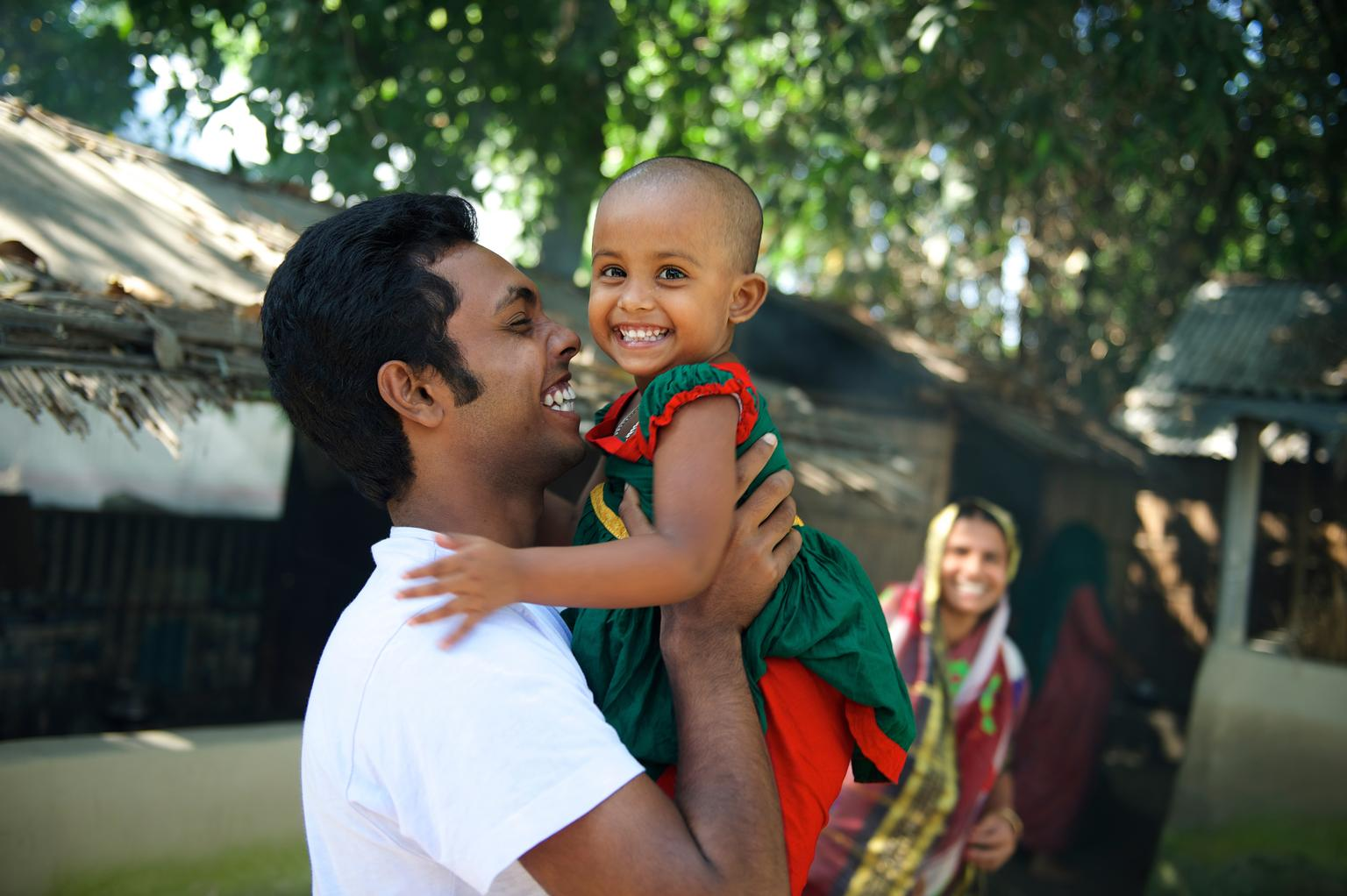 A young girl from Bangladesh smiles as her uncle picks her up.
