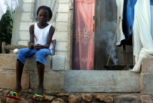 11-year-old Djolanda sits outside her home.