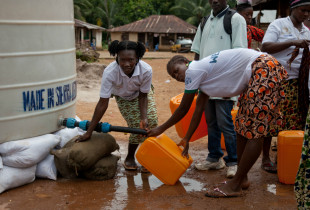 Kadiatu Konteh (left), an Ebola Survivor, delivers water, supplied by UNICEF, for villagers under Ebola quarantine