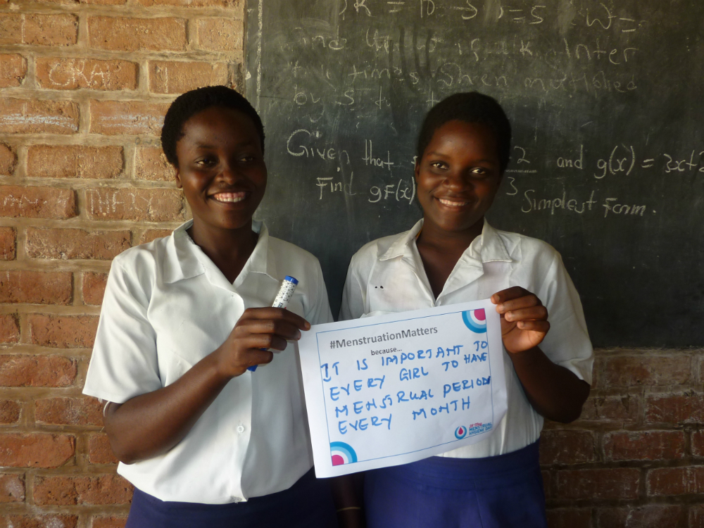 Two school girls in Malawi hold up a sign explaining why they believe menstruation matters.