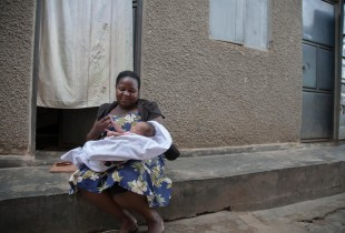 Mother of 4, Mantume Christine holds her newborn baby girl outside the family home in Uganda. Her newborn daughter will receive her birth certificate that same day.