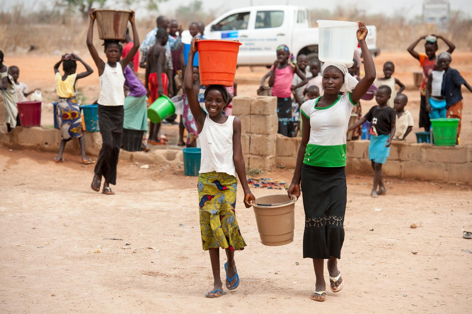 Girls carry buckets filled with water in a camp for internally displaced people, outside Yola in Nigeria.