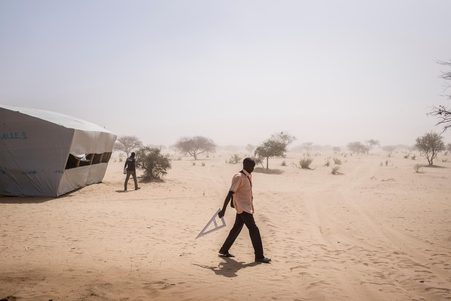 A teacher walks home from a temporary learning space at the end of the school day, in the Dar es Salam camp.
