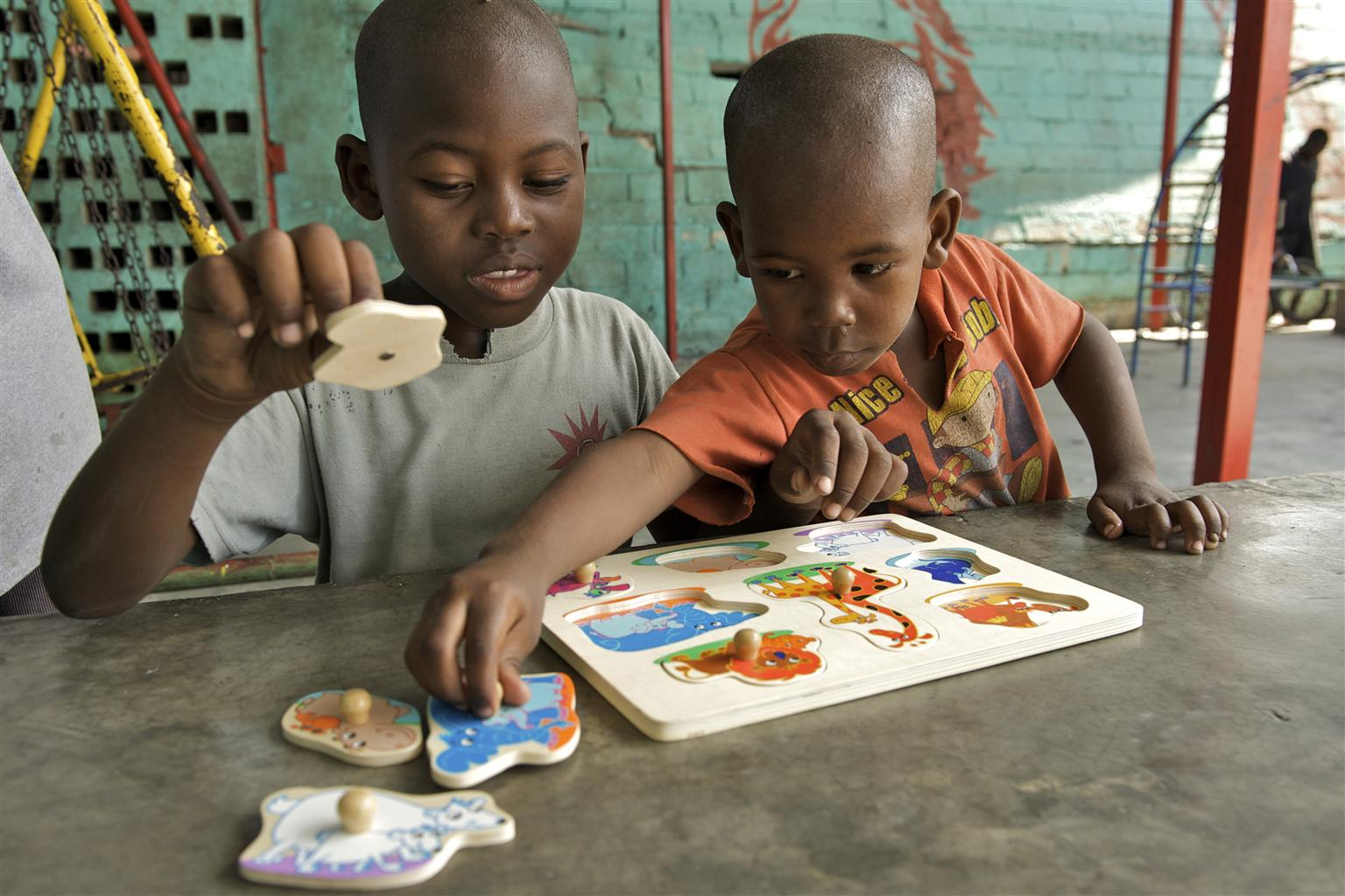 In Haiti, Steve (8) and Richard (5), play with a board puzzle from a UNICEF ECD kit.