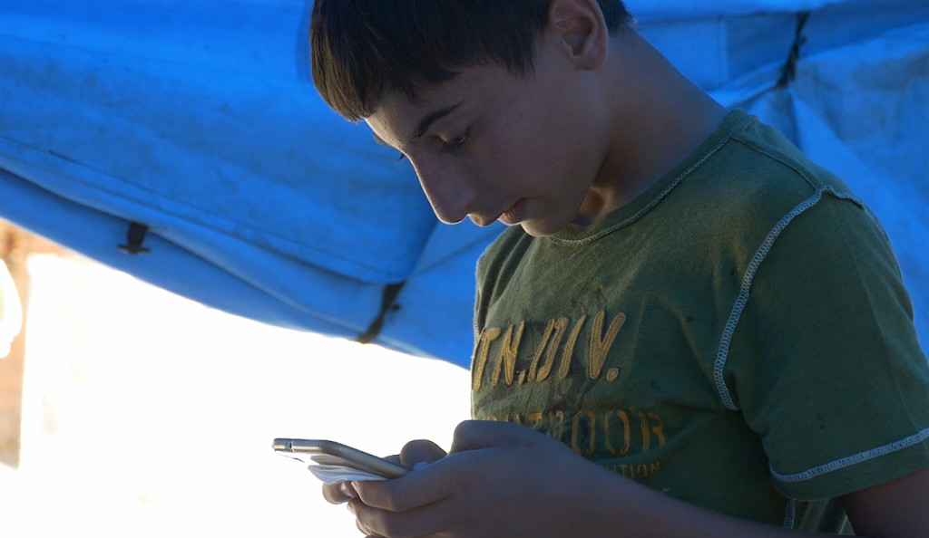 Jehad, 15, from Syria checks his instant messaging service on his mobile phone.