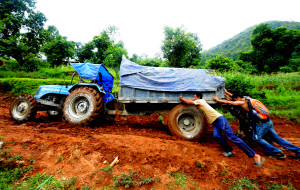 The tractor, stuck in the mud on the road to Simjung, is pushed back on track.