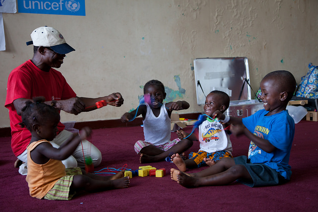 Young children play with games included in the Early Childhood Development kit at the Child Friendly Space in Freetown. More than 500 children have been registered at the space.