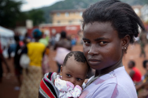 A mother holds her baby with displaced flood victims in the background