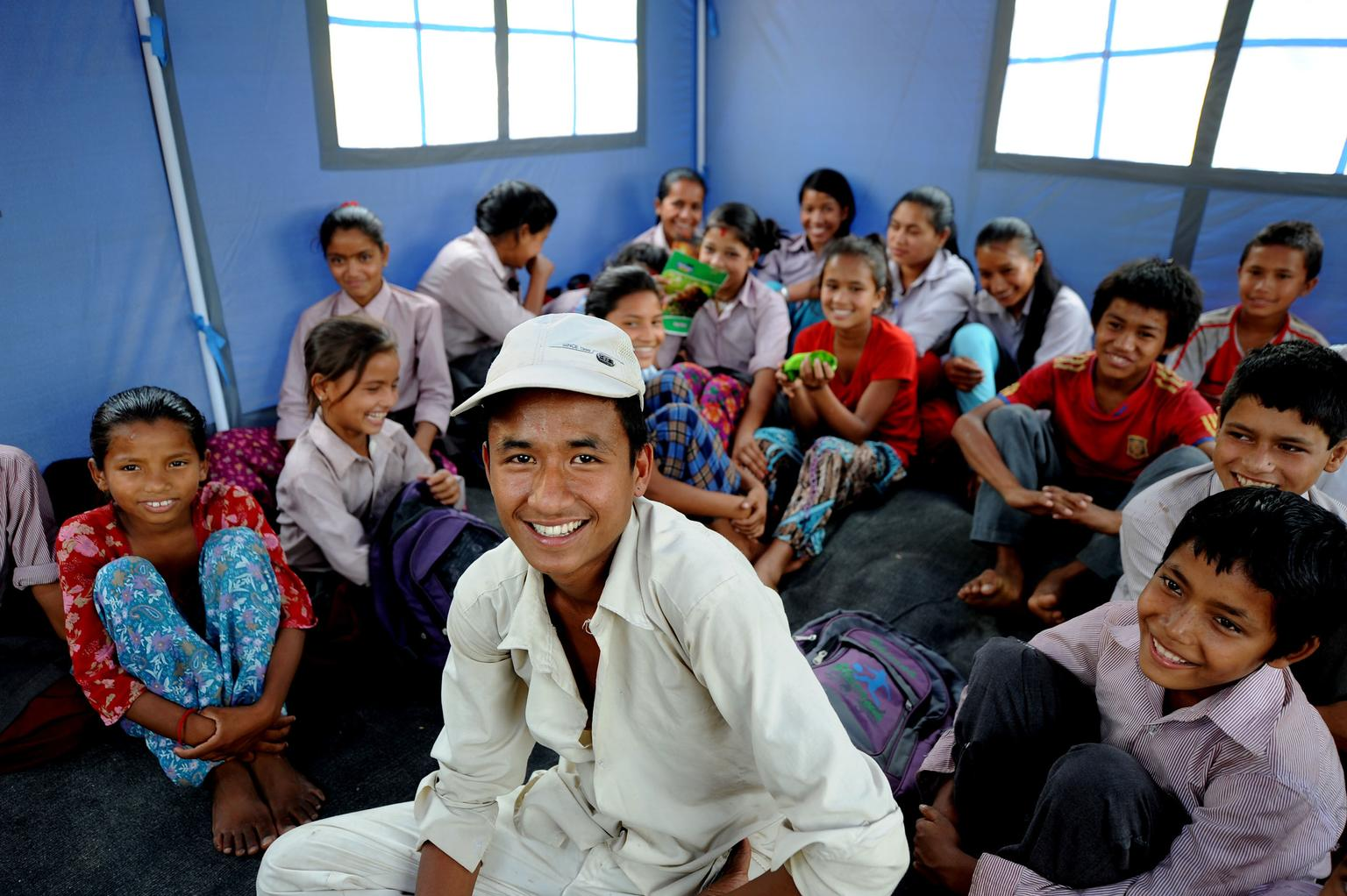 A young teacher, in front of his students in a makeshift classroom.