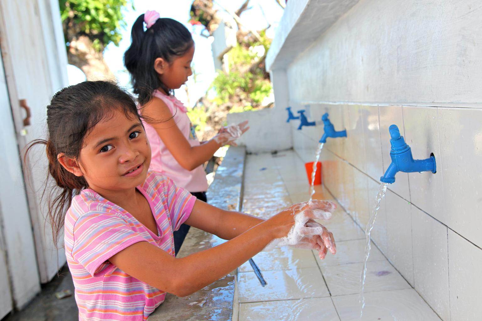 Venus (8) washes her hands with soap and water at a new hand-washing facility at her school in the Philippines.