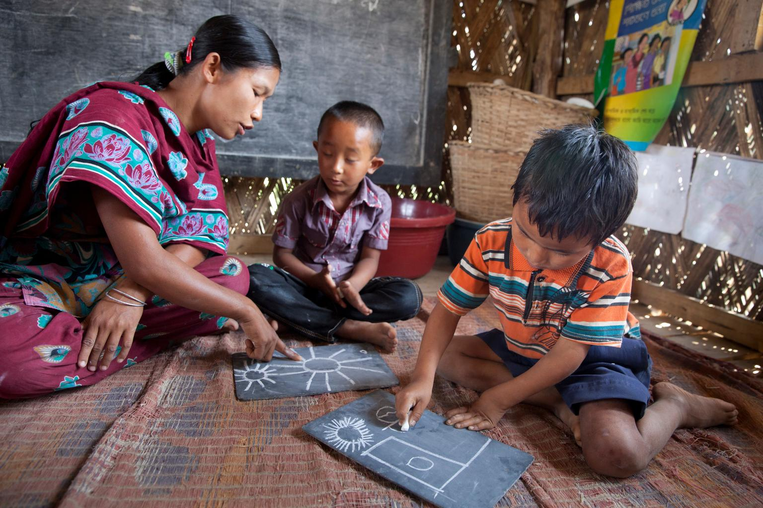 Chinta Debi, helps children with their drawings during classes at the Murungkhang Para Centre in Rajbila, Bangladesh.