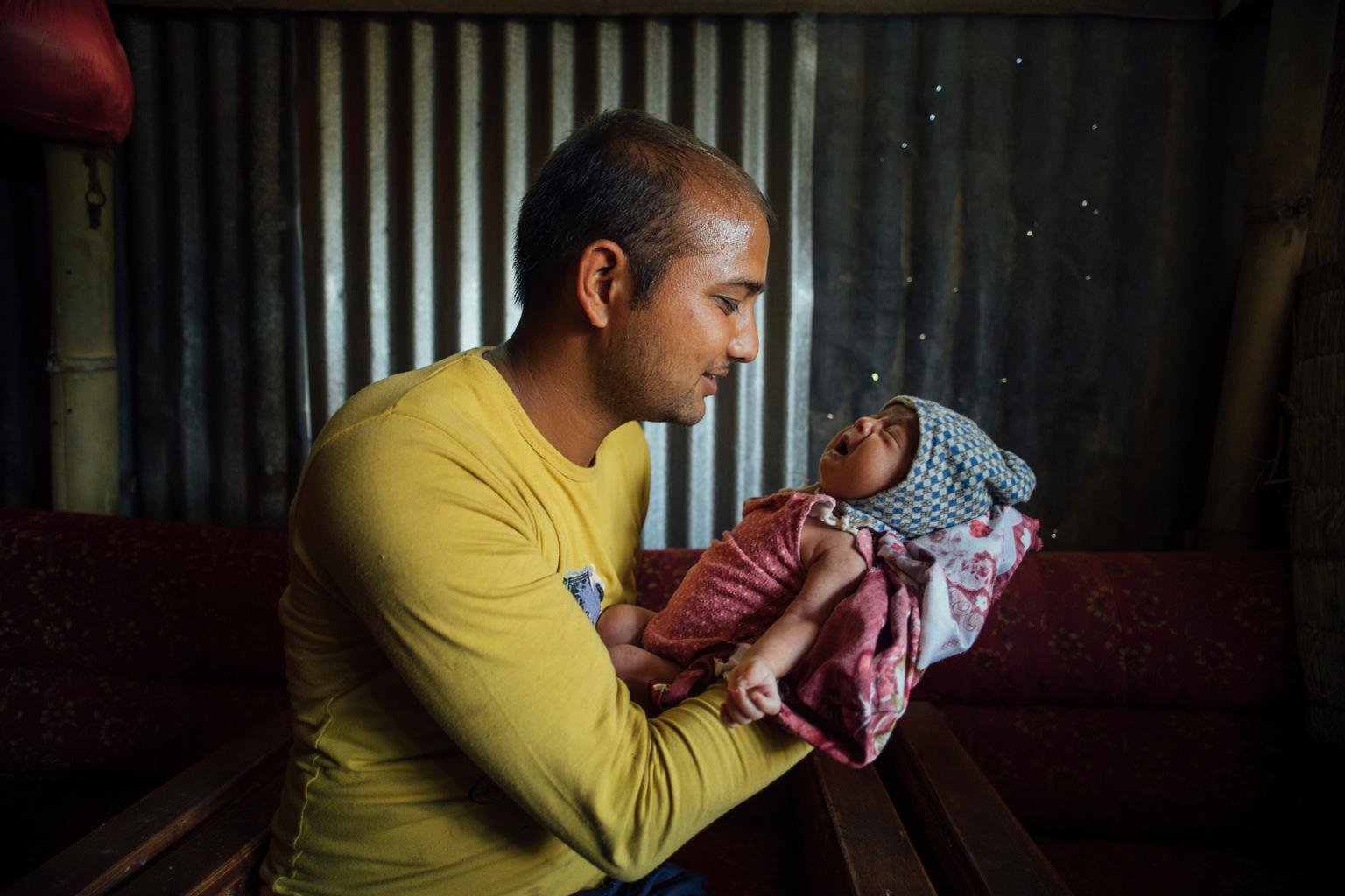A father holds his 22-day-old son, who was born in the period between the first and second earthquakes in Nepal this year.