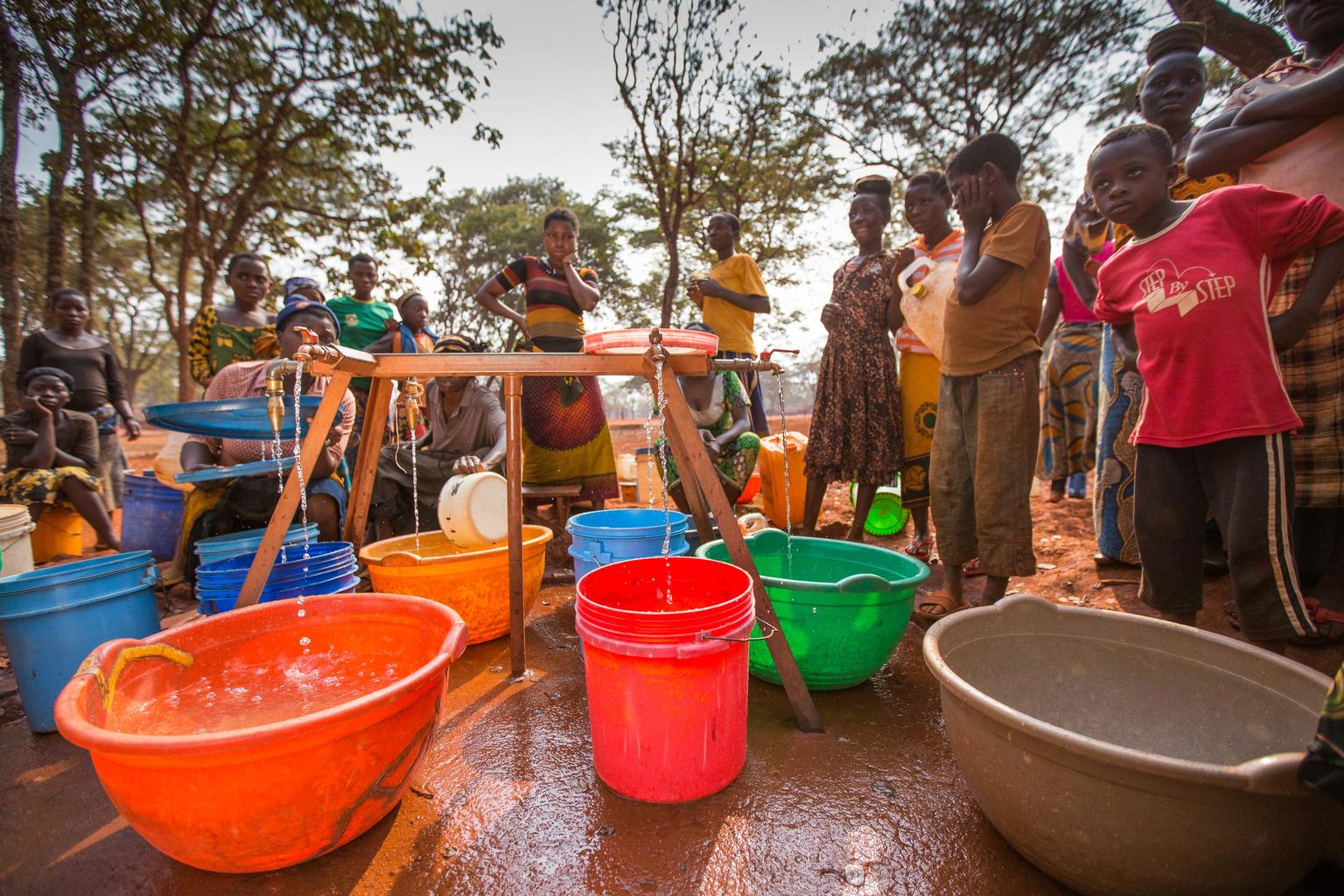 In June 2015, Congolese girls and young women fill their water containers in the Nyarugusu refugee camp in Tanzania.