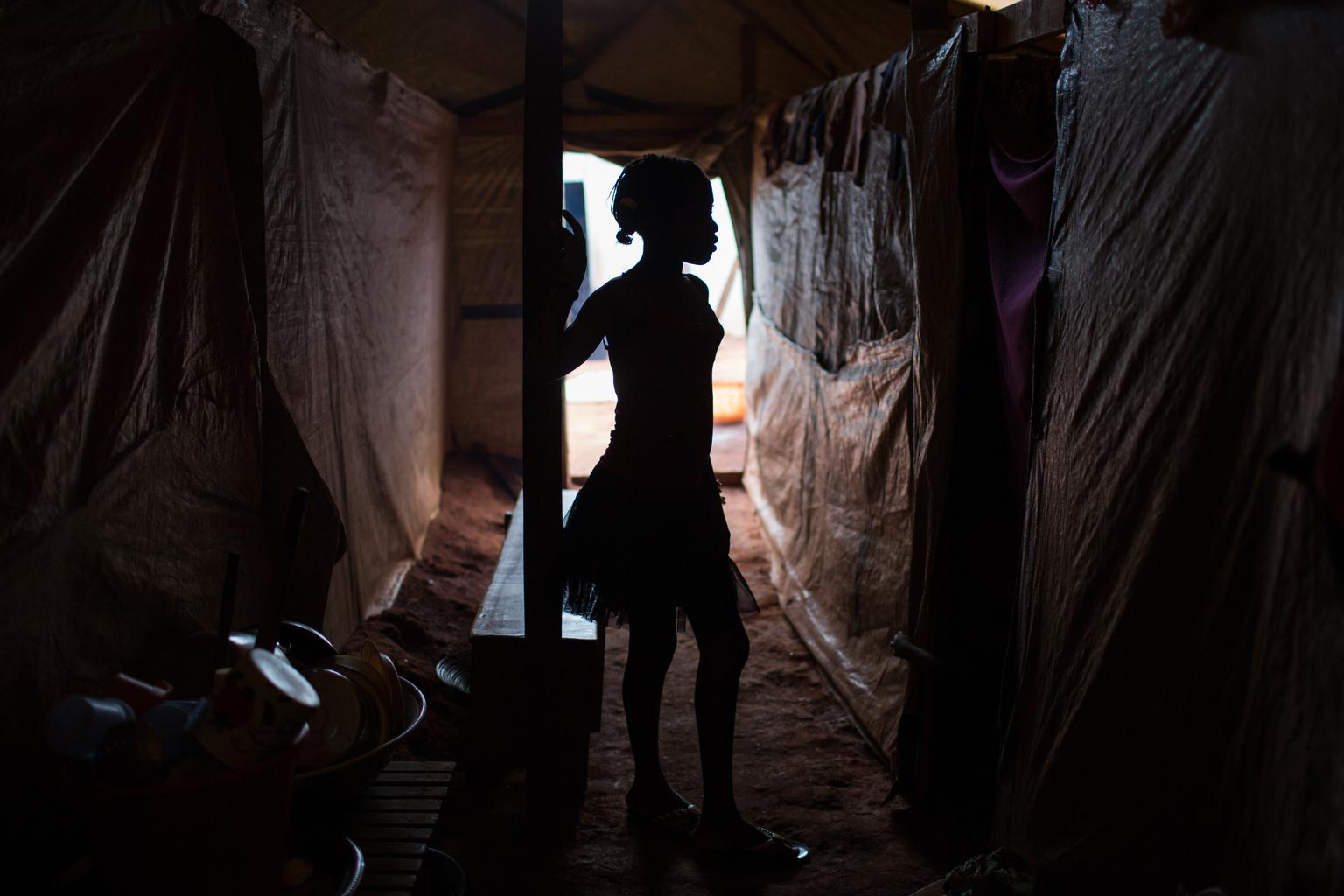 Back in June, Alison, (14) stands beneath a makeshift shelter at a site for internally displaced people, in Bangui, the capital.