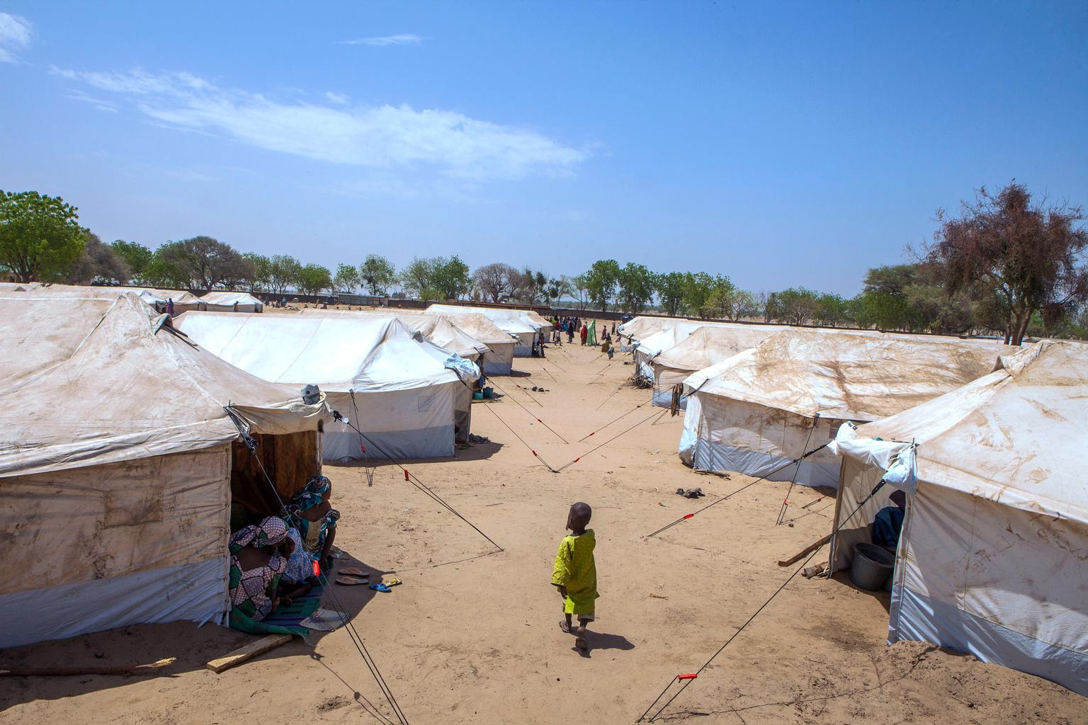 A child walks between rows of tent shelters in the UNICEF-supported Dalori camp for internally displaced people, in the north-eastern city of Maiduguri, Nigeria.