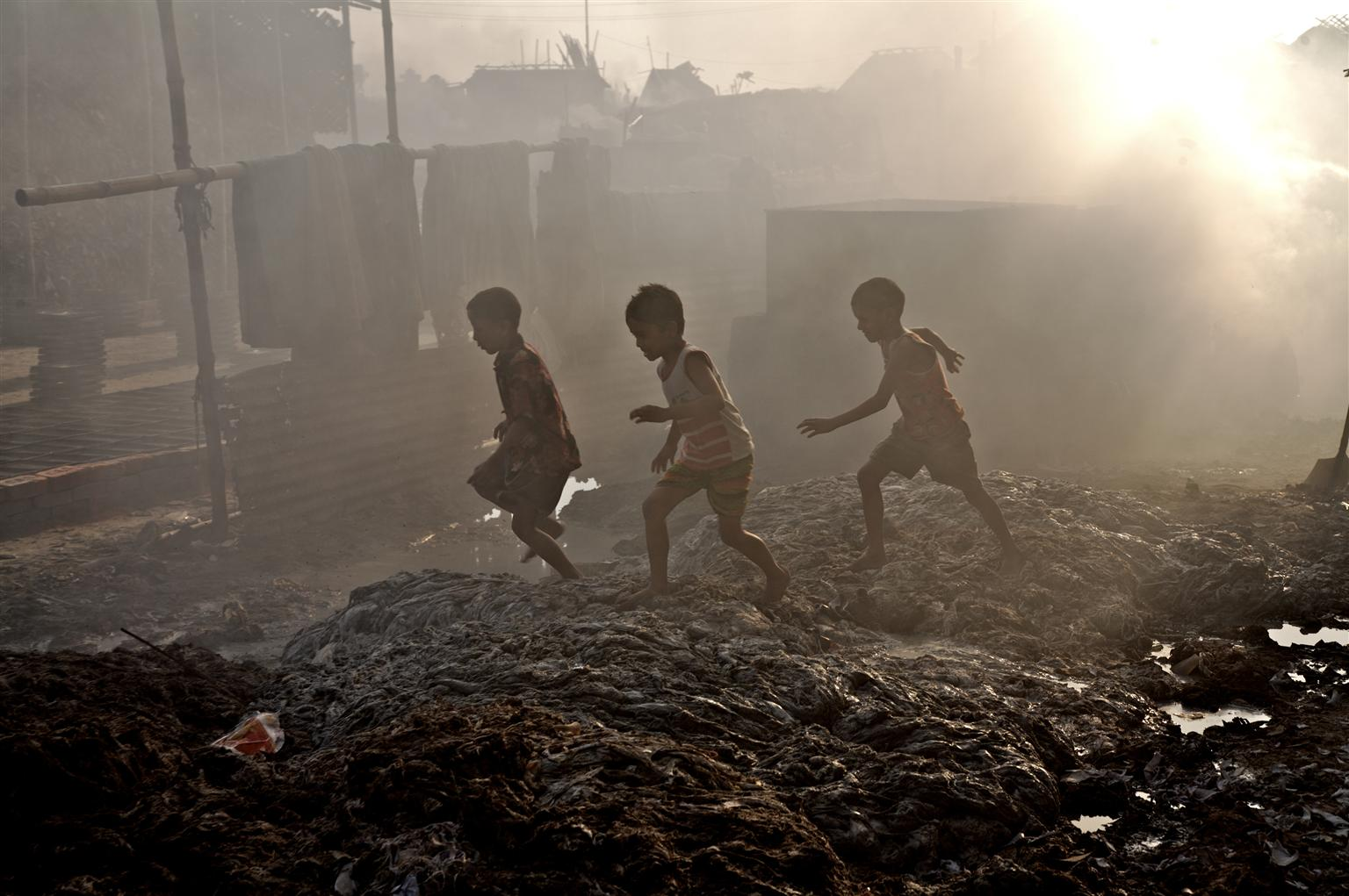 Child Poverty - 7 facts about poverty - Children play outside their home that has been turned into a large dumpsite by waste from leather industries in Bangladesh.