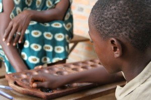 Close up of a boy playing a game with a wooden board.