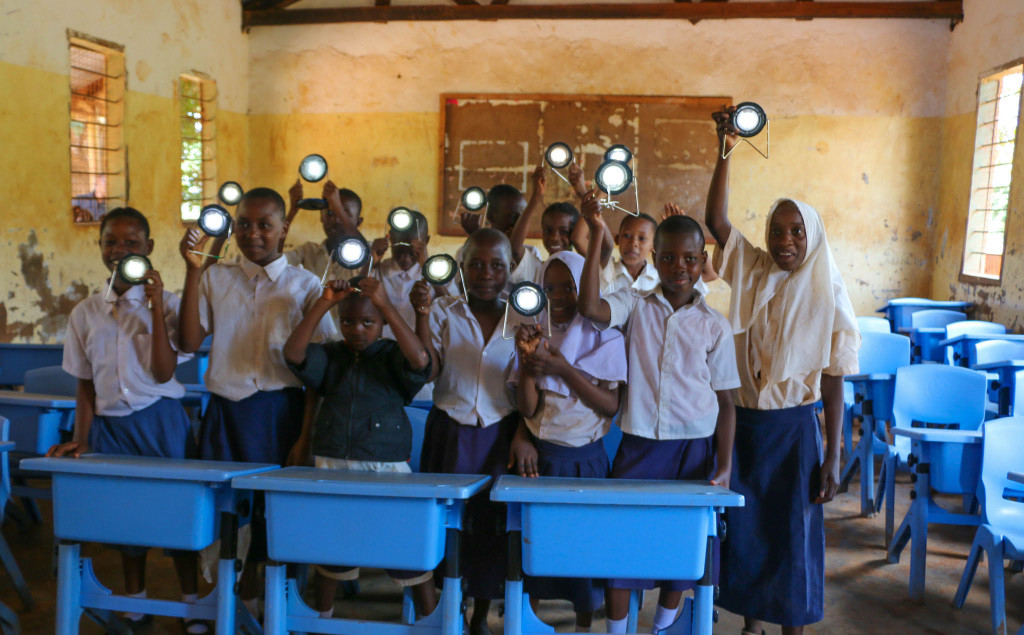 A classroom of students hold up innovative projects they've created.
