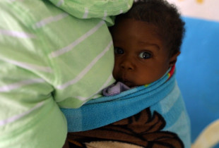 A very small baby, strapped to her mother's back, waits to get registered.