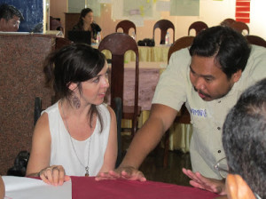 A young woman working at a table with a man beside her.