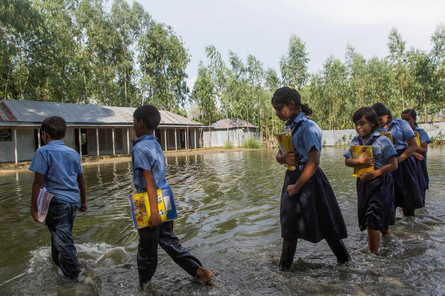 A group of uniformed students walk through water.