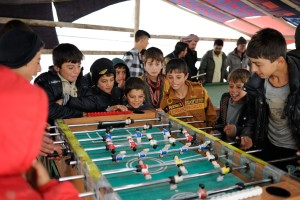 Boys stand around a foosball table.