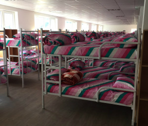 A series of bunk bbeds set up in a dormitory.