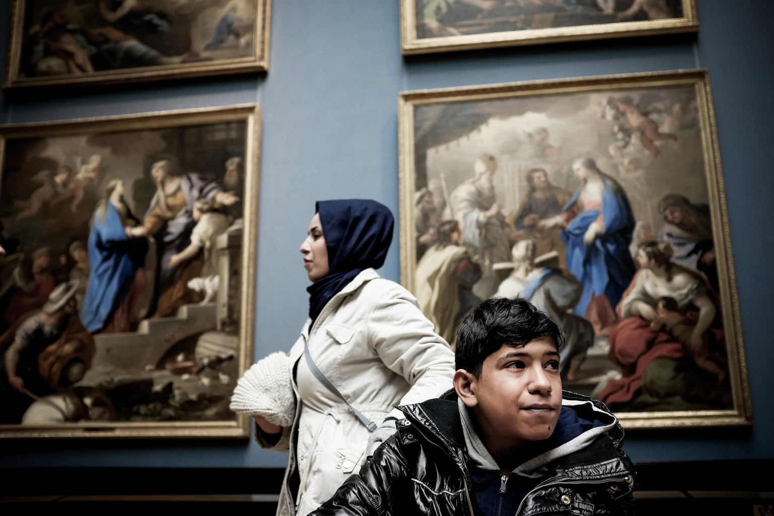 A mother and son in front of a painting.