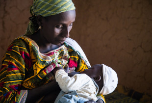 A woman breastfeeding a child.