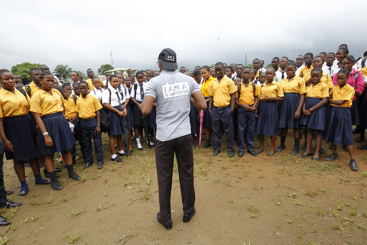 A young man addressing a group of people.
