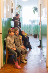 A line of children sit on a bench in a hallway.