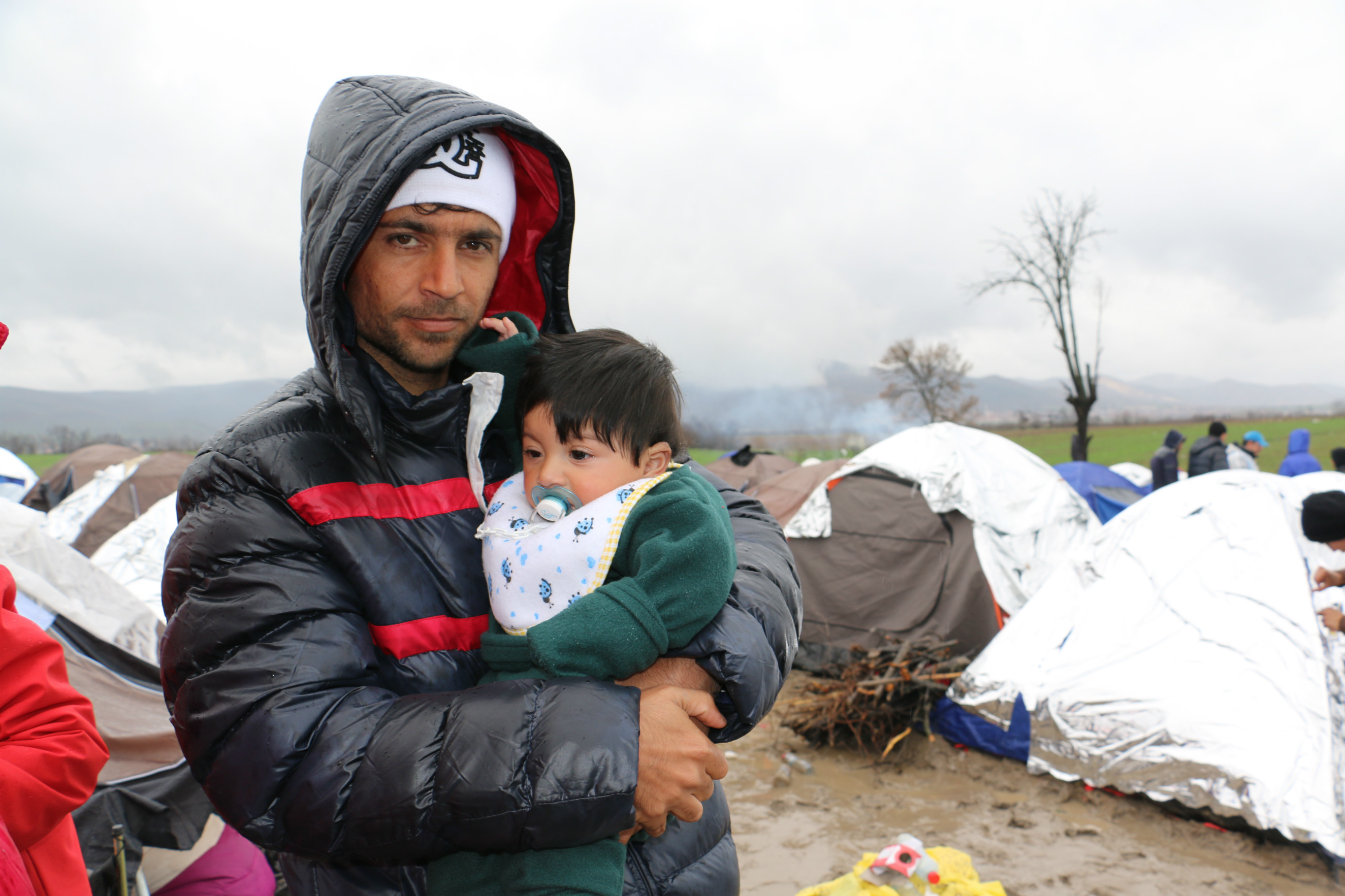 A man stands outside holding a baby.