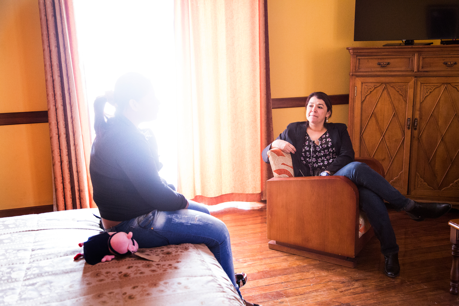 Two women sit in a room, one's face is blurred.