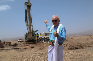 A man points at a very large drill.