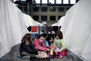 Four girls sitting on the ground, playing at a refugee camp. UNICEF photo