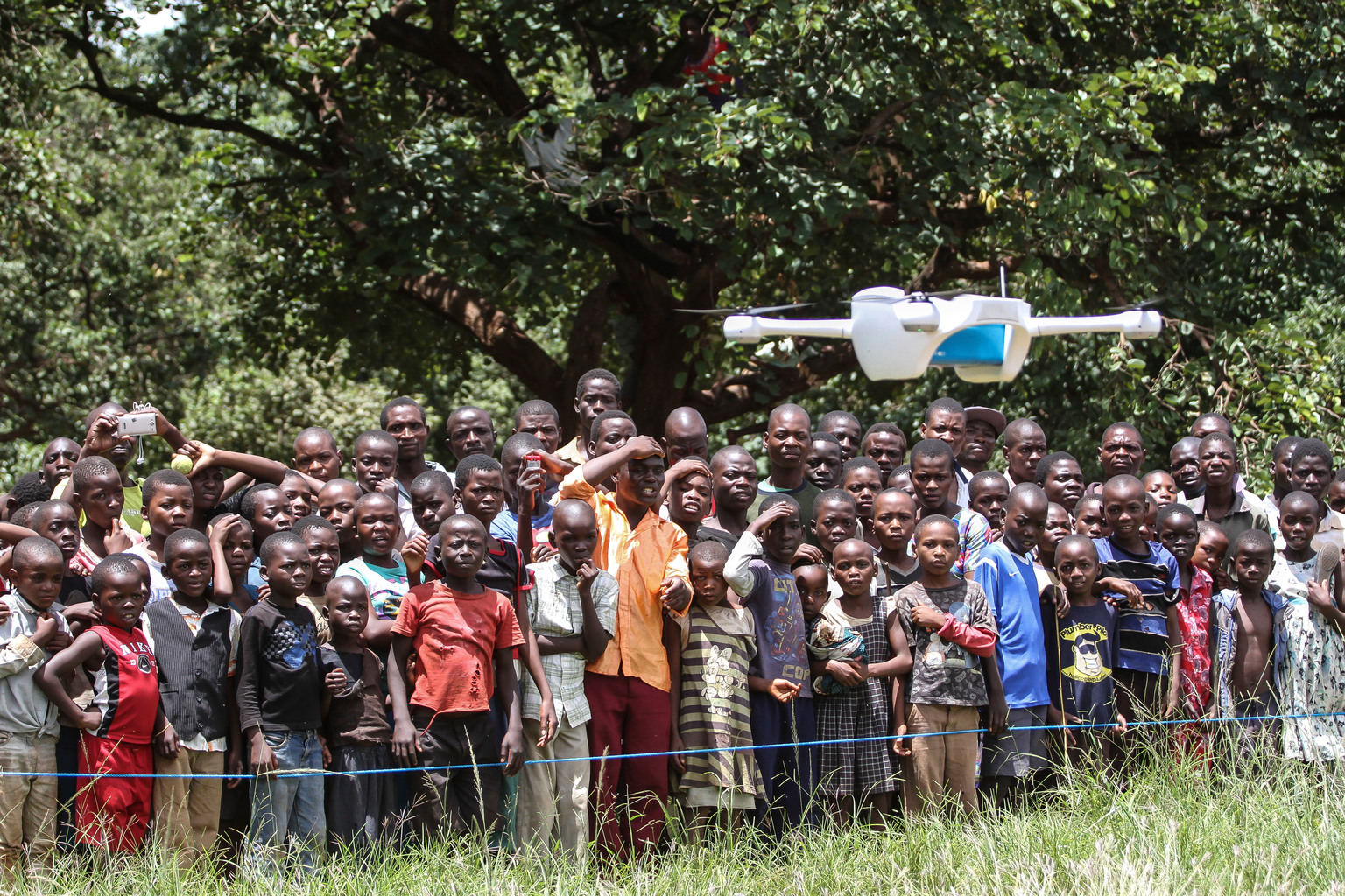 A group of children looking at a drone.