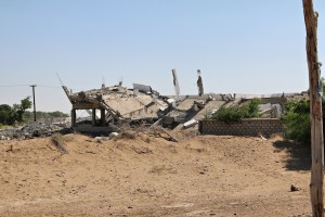 An image of a destroyed school, covered in sand.