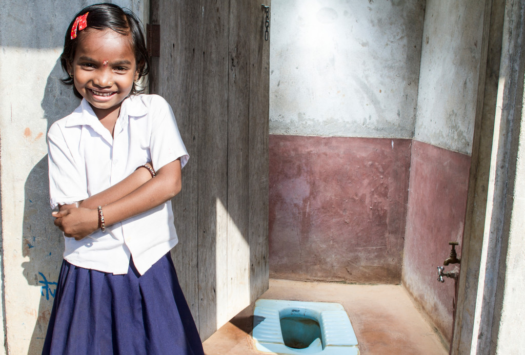 A young girl stands by her toilet.