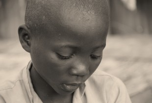 A close-up of a young boy staring down.