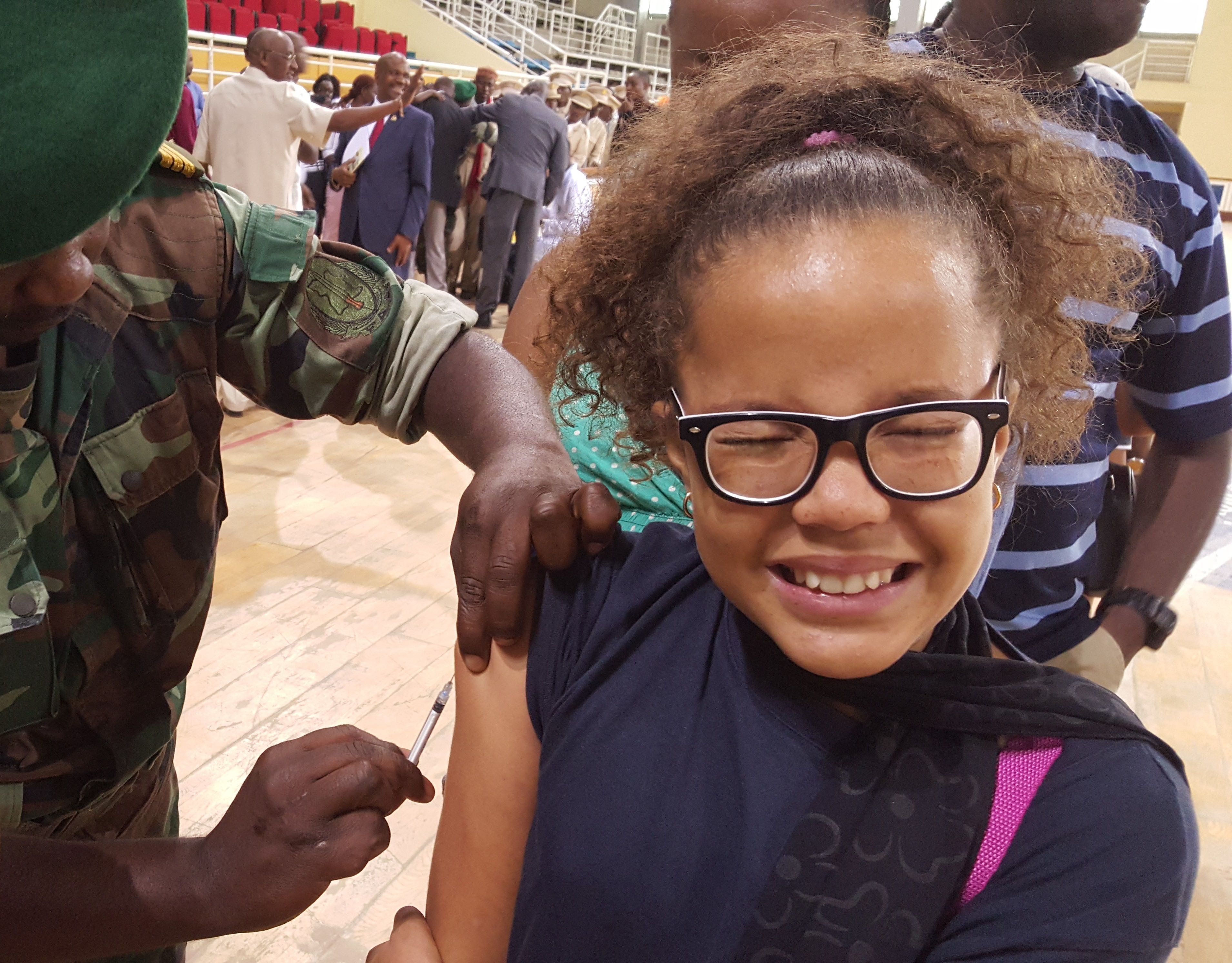 The face of a young woman receiving an injection.