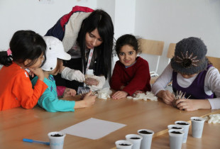 Children making crafts at a table.