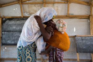 Fati, 15, hugs her mother Mariam while carrying her sister at the Minawao refugee camp in Northern Cameroon. She was abducted by Boko Haram and was eventually freed by Cameroonian soldiers and has been reunited with her family in a refugee camp in Cameroon.