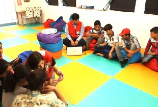 A group of kids on the floor, working with computers.