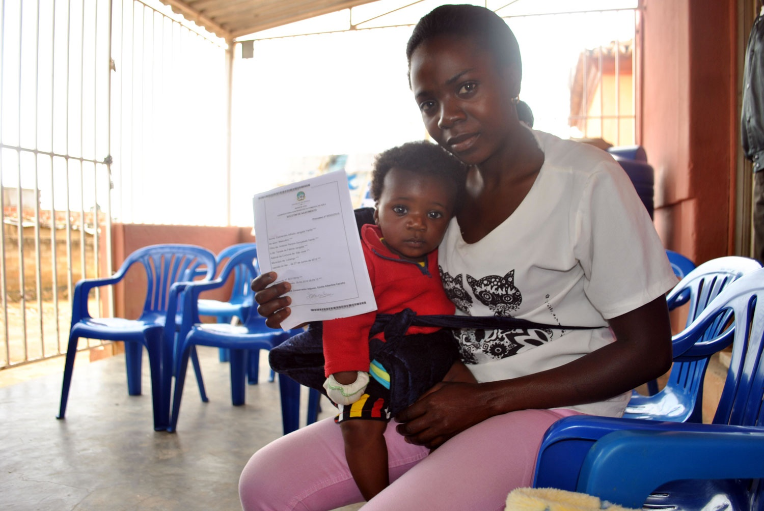 A woman with her child showing a paper.