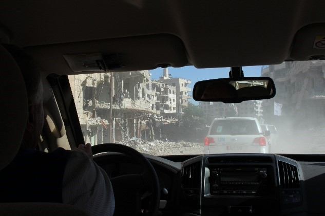 A scene of bombed buildings through a car window.