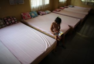 A young girl sits on a bed with a book.