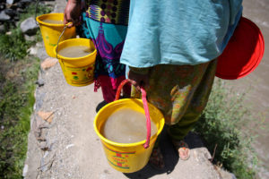 Buckets of murky river water carried by women and girls