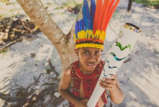 A boy in headdress holding a torch.