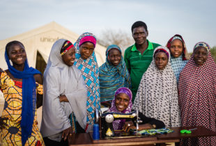 Young girls and man around a sewing machine
