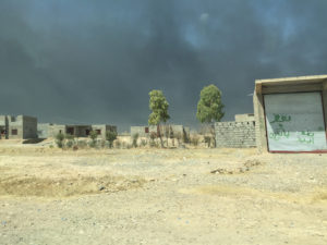 Abandoned houses in dusty field with dark smoke from oil fires in the background